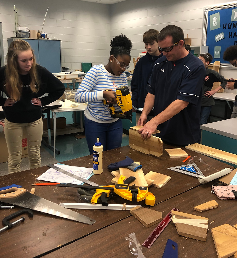 Richardson and seventh-grade students working on the construction phase of the birdhouse.