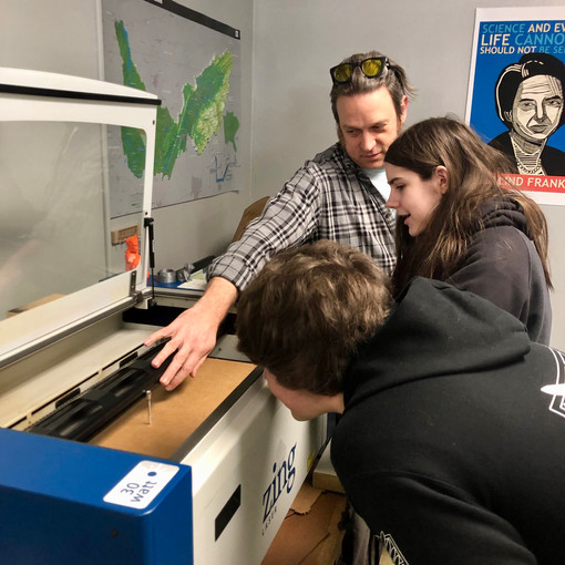 Matthew Craig reviews the laser cutter process with students.