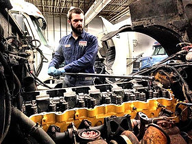 Universal truck service employee using a crow bar to tune up a truck engine