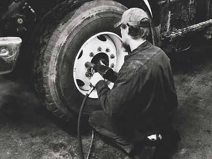 Universal truck service employee changing a tire on a semi truck