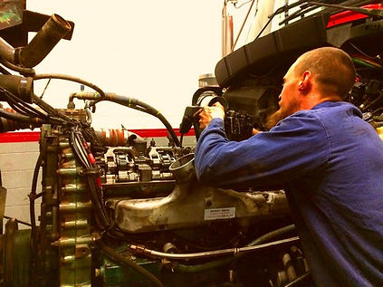 Universal truck service employee working on a semi truck engine