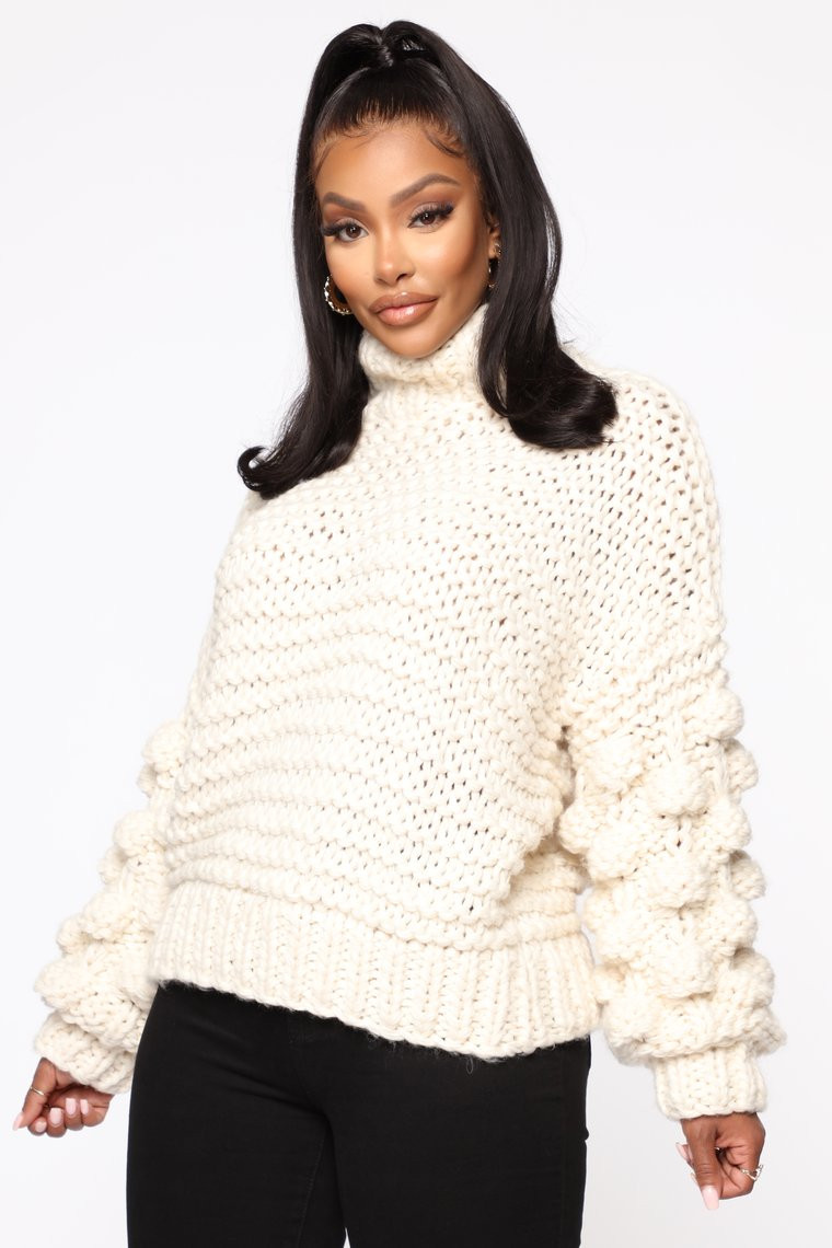 A woman wearing a creme-colored chunky cable knit sweater with puff sleeves and chic texture.