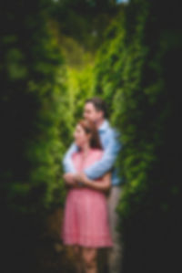 a couple holding each other surrounded by green trees Mohonk Mountan house