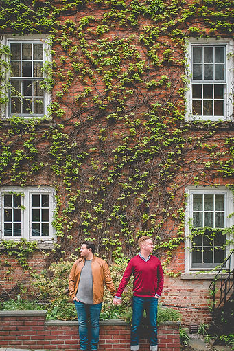 2 gay men holding hands in front of a building covered in ivy
