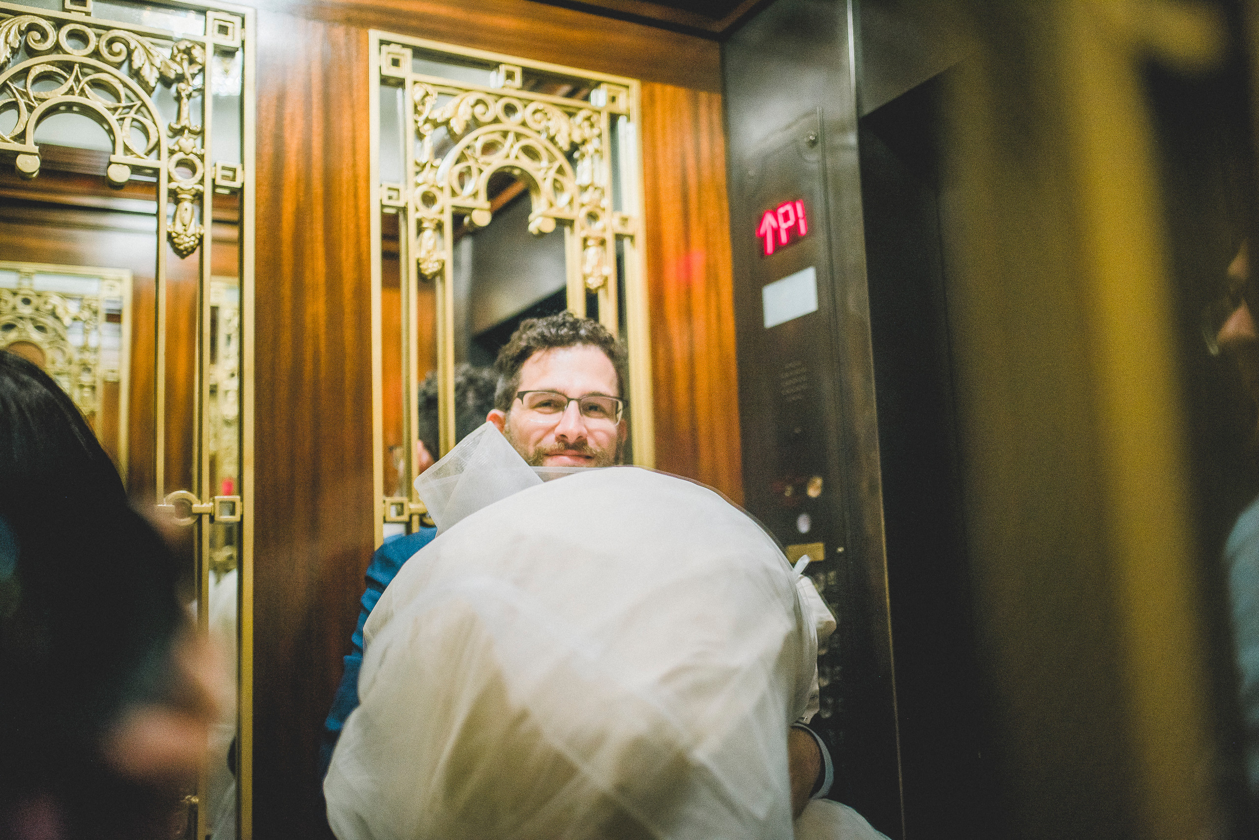Groom holding brides dress in Plaza Hotel Elevator NYC Wedding