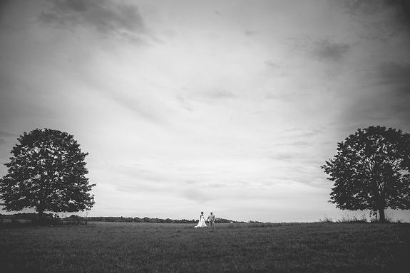 black and white image of Bride and groom in a field between two trees