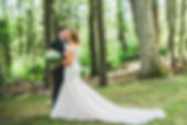 bride and groom kissing at first look in the woods