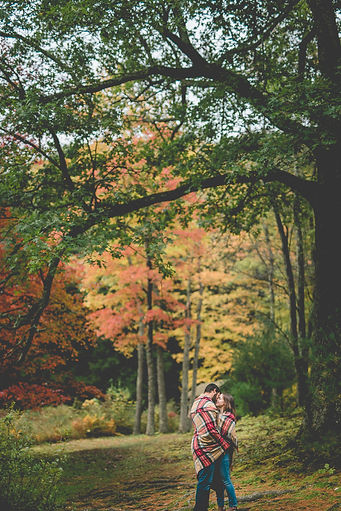 a couple wrapped in a blanket in the fall woods kissing