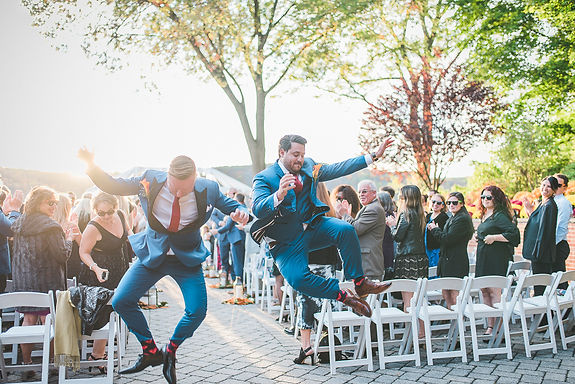 two grooms jumping for joy coming down the aisle from gettig married
