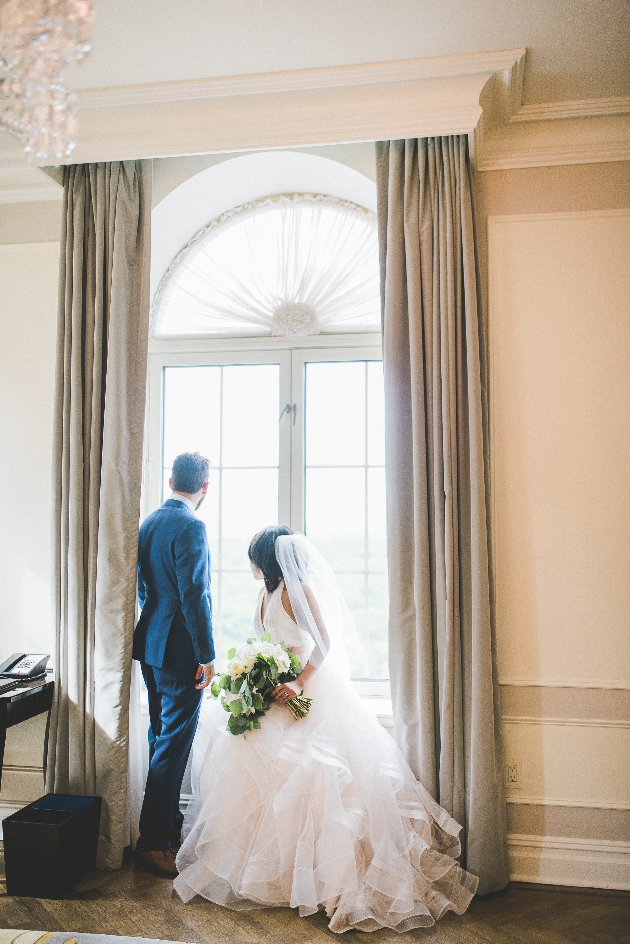 Bride and groom in Plaza Hotel Suite looking out Picture Window NYC wedding inspiration