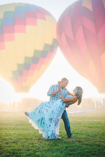 a couple dancing at sunrise with hot air balloons in the back
