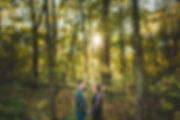a couple holding hand in the woods with the sun coming through the trees