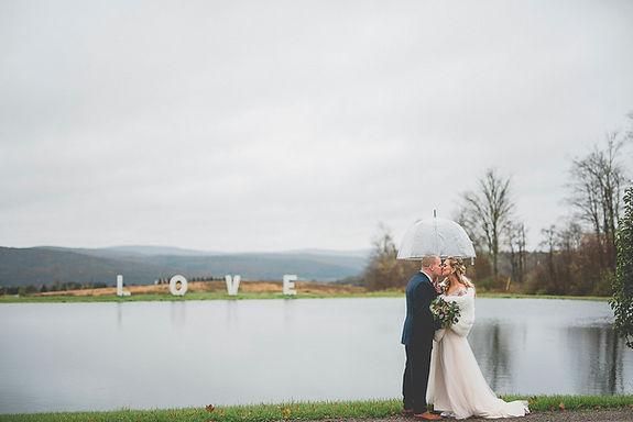 Bride and groom kissing in the rain under an umbrella