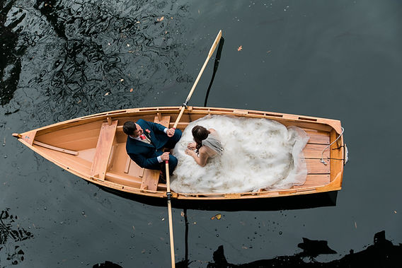 Bride and groom in a row boat on a lake from above