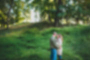 A couple holdin each other in front of a grassy hill