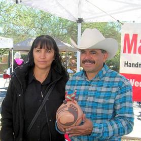 Jerardo Tena holding his pottery.