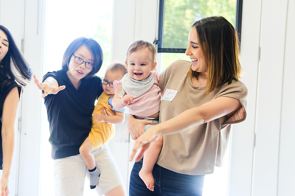 Moms and babies dancing and singing in bilingual music class