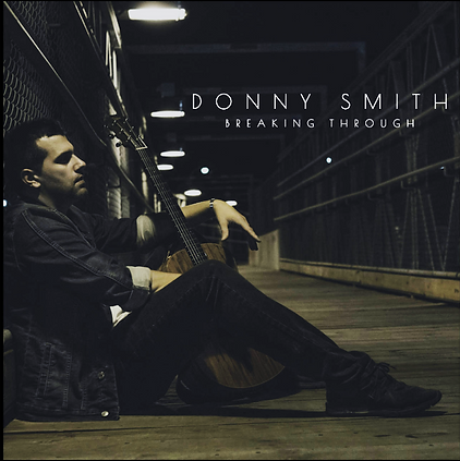 A photo of musician Donny Smith at night sitting on the floor of a covered bridge. Donny Smith is a Toronto based songwriter, vocalist, and guitarist whose music is pushing the limits of the pop genre, combining edgy blues/funk riffs with bright, infectious melodies.