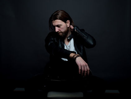 A seated photo of rocker musician Jeff Smith who is a Canadian-based singer-songwriter, performer, musician, and vocalist. His exceptional vocal range is described as husky and gritty that exudes passion.