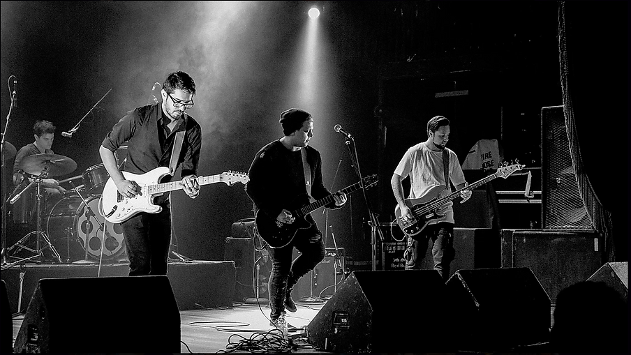 A black and white photo of Toronto band City Circuits performing on stage with dramatic lighting.