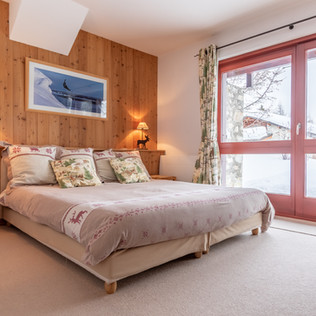 Chambre 2 avec grande baie vitrée donnant sur une terrasse sud-ouest