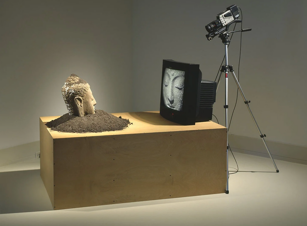 Buddha head sculpture on pedestal facing tv & film camera which is recording and playing back a live video of Buddha's Face.
