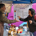 stall holder taking money from a customer at an outdoor vegan market
