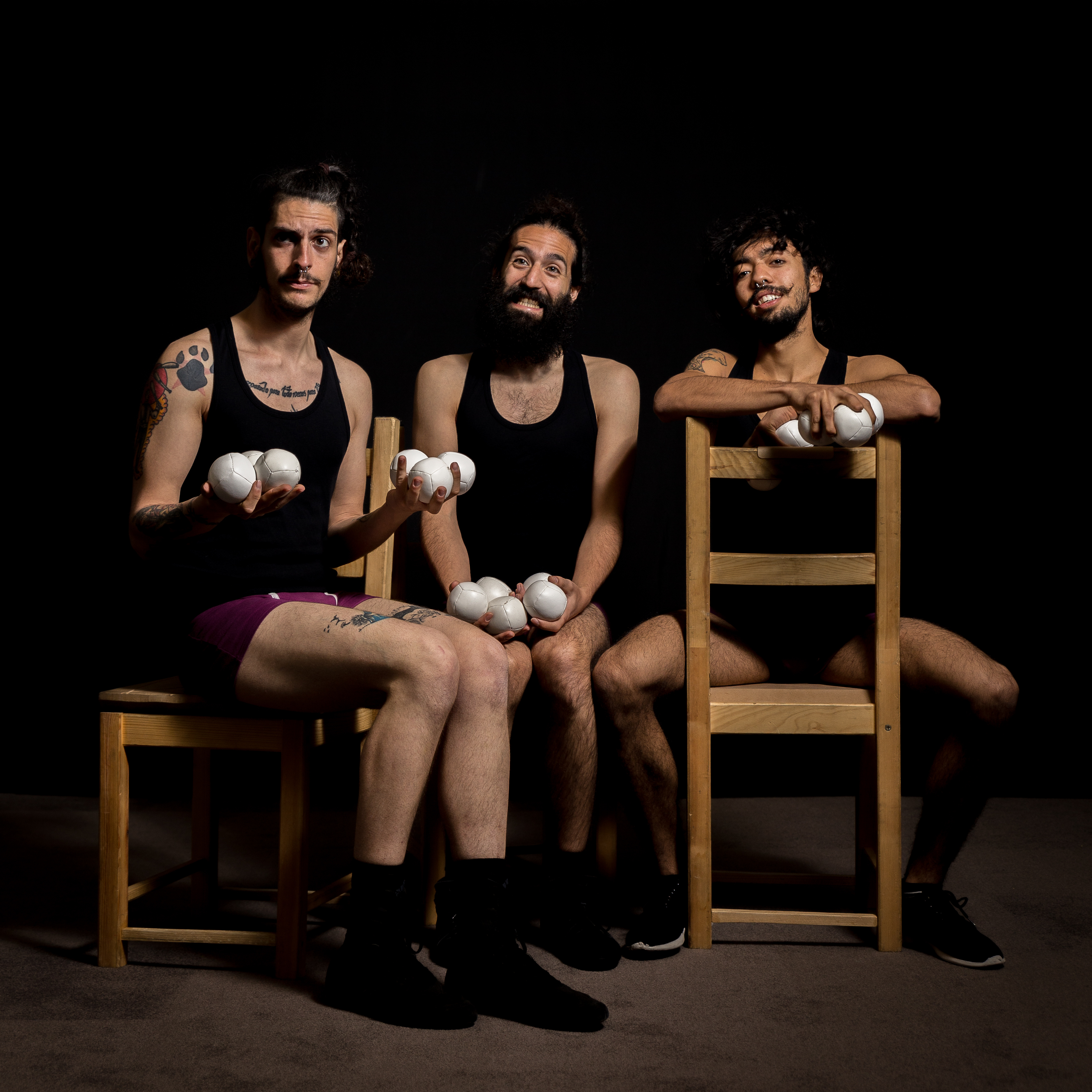 3 circus performers sit in chairs holding juggling balls in front of a black backdrop