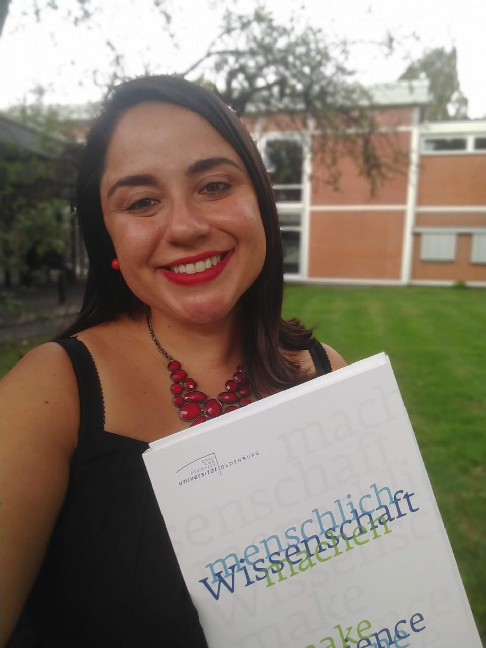 Young woman taking a selfie holding her diploma and smiling.