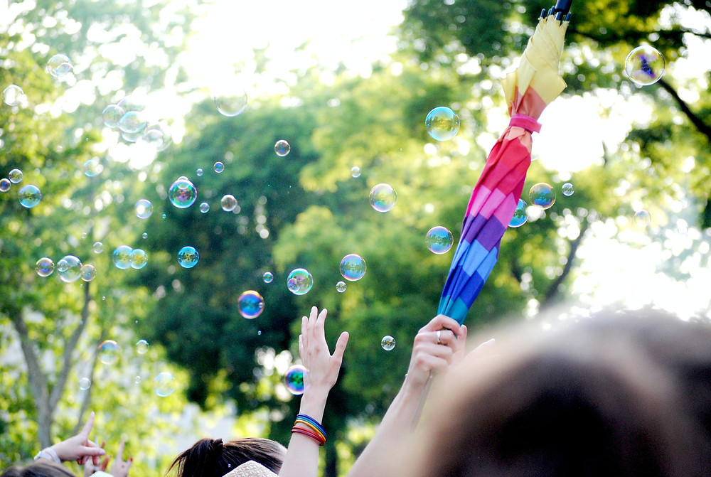In the foreground, some hands reaching up, someone holding a rainbow umbrella, folded, high in the air, and bubbles someone's blown. Trees in the background.