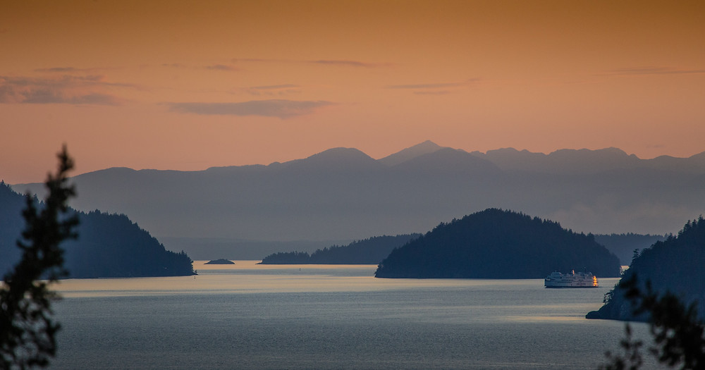 A photo of Howe Sound, BC at dusk - islands scattered in the calm ocean with a ferry moving between two of them.