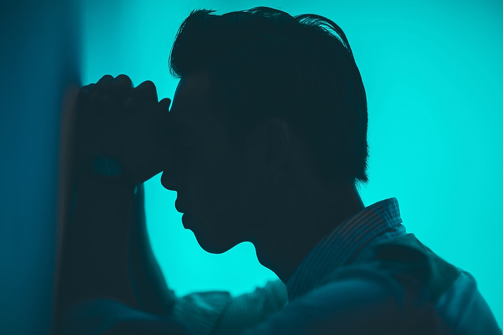 A silhouette of a man facing a wall with his fists between his forehead and the wall. He is wearing a white shirt. The background is blue.