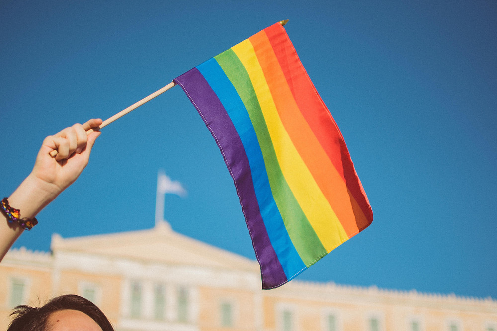 A hand holds a rainbow flag with a government building in the background.