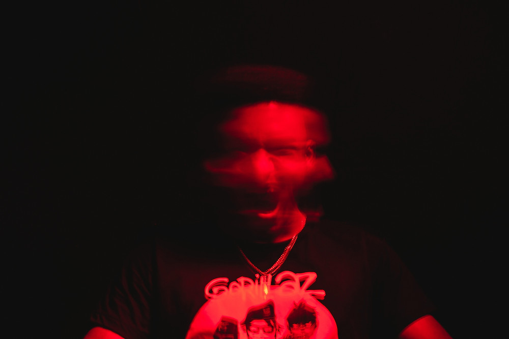A black man is lit in red and is blurred from moving his face back and forth with mouth open.