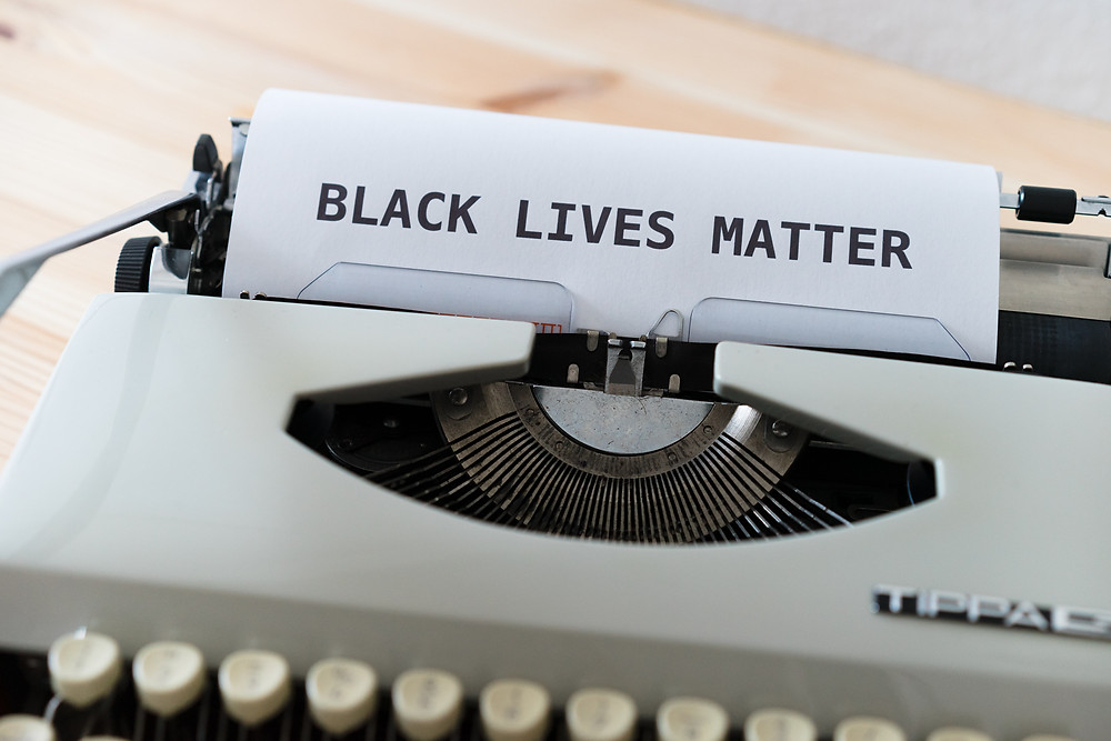 "An old fashioned typewriter has printed the words in all caps: ""BLACK LIVES MATTER"""