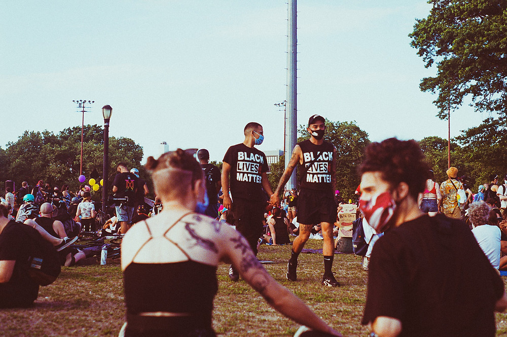 "Two men wearing ""Black Lives Matter"" t-shirts and shorts walk hand in hand among a crowd of seated people on grass."