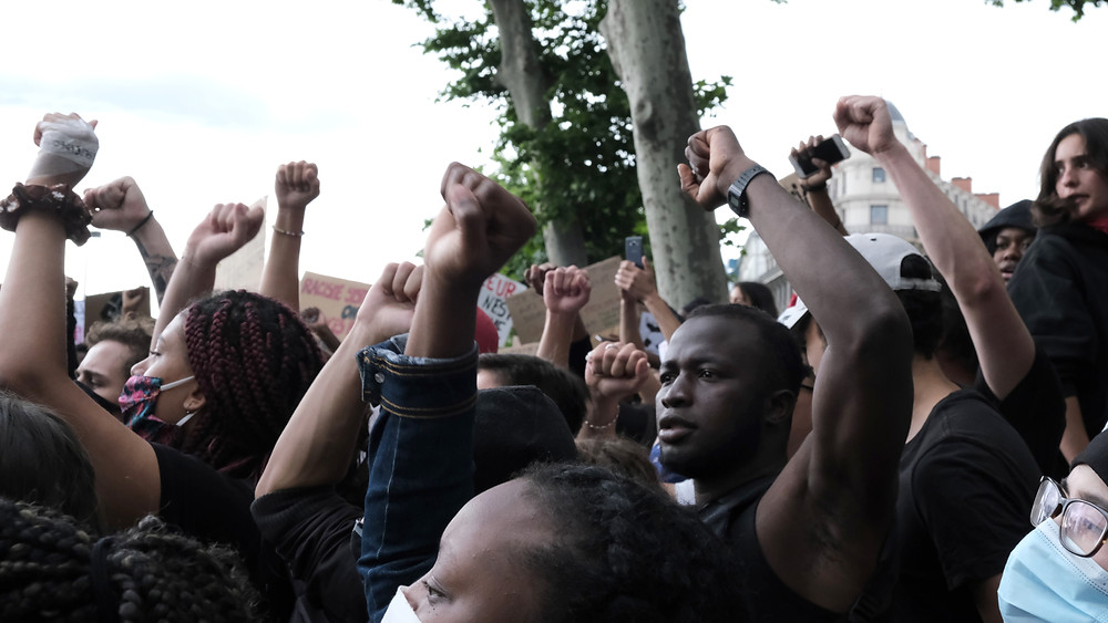 A crowd of black people stands outdoors with upraised fists.