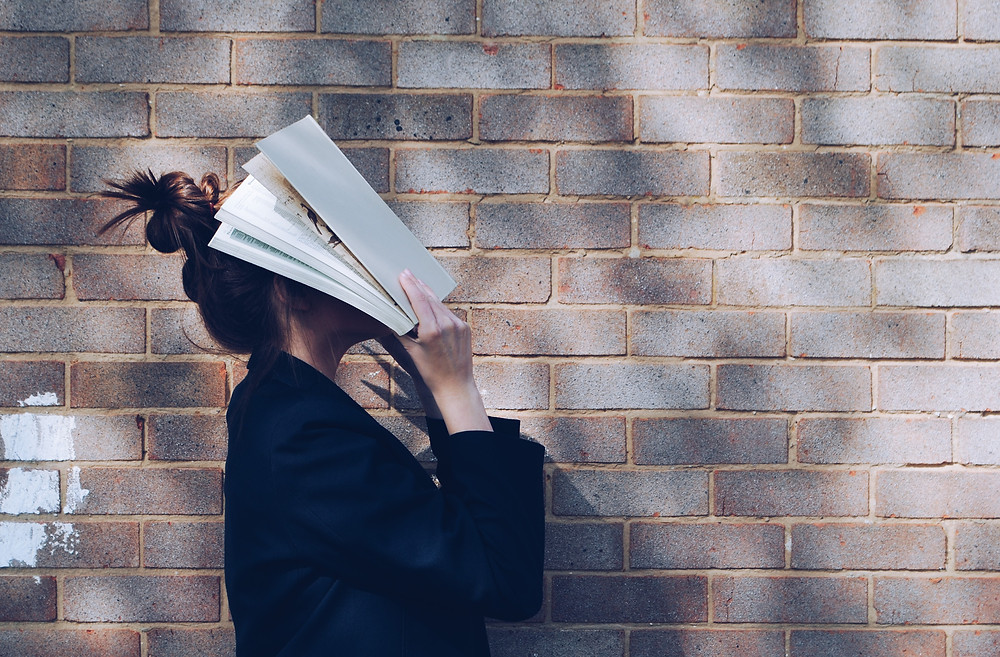 Woman in front of a brick wall holding a book up to her face.