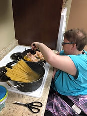 Adult cooking pasta in wheelchair