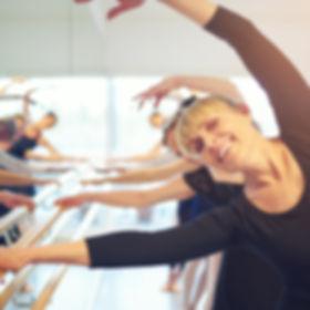 Cheerful mature female ballet dancer sta