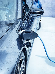 Electric vehicle being plugged in.jpg
