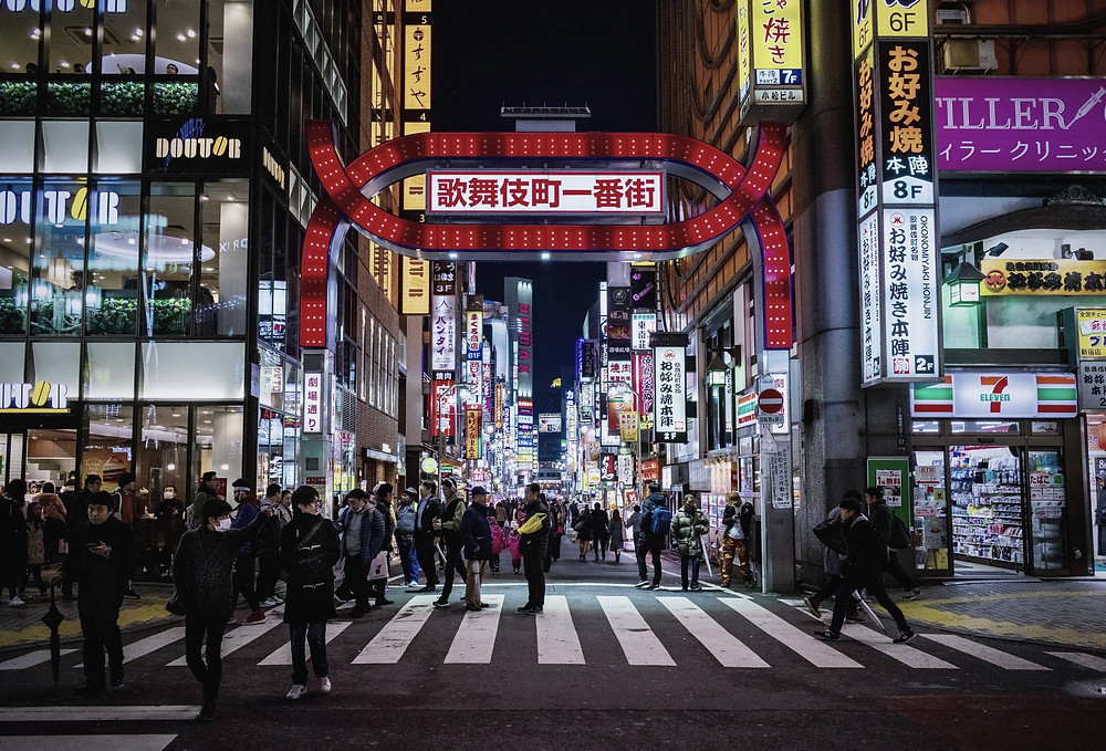 Image: a busy street at night in the city centre of Tokyo