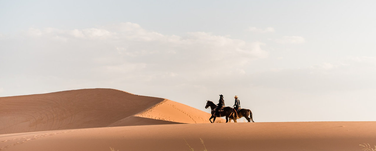 a couple riding their horses in the Coral Pink Sand Dunes, in Kanab, Utah