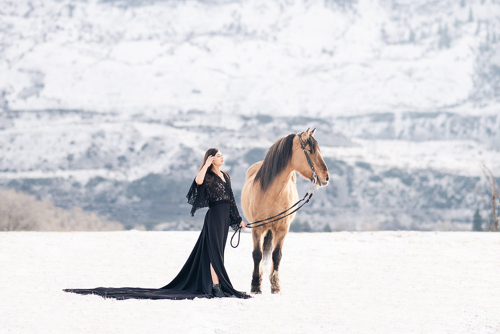 a girl wearing a long black dress standing in snow with a mountain in the background, with her buckskin horse