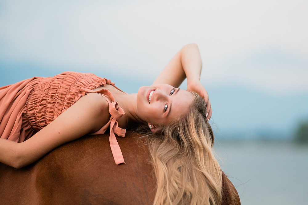 Riley Rocholl, a blonde high school senior girl, laying on the back of her horse smiling at the camera
