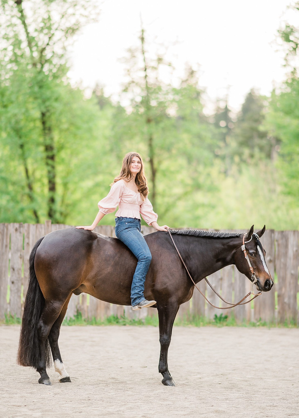 a girl wearing Kimes jeans and a pink shirt, sitting on her AQHA bay gelding