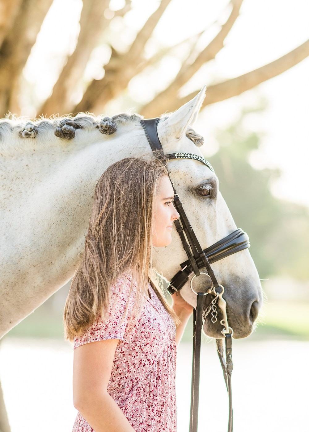 Jordan, a working student at Helgstrand Dressage standing next to her grey Andalusian stallion both looking off in the distance. A headshot from waist up