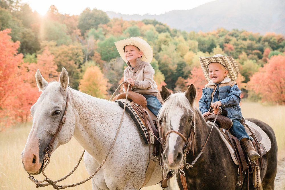 the boys, Tatum and McCoy sitting on their horses laughing