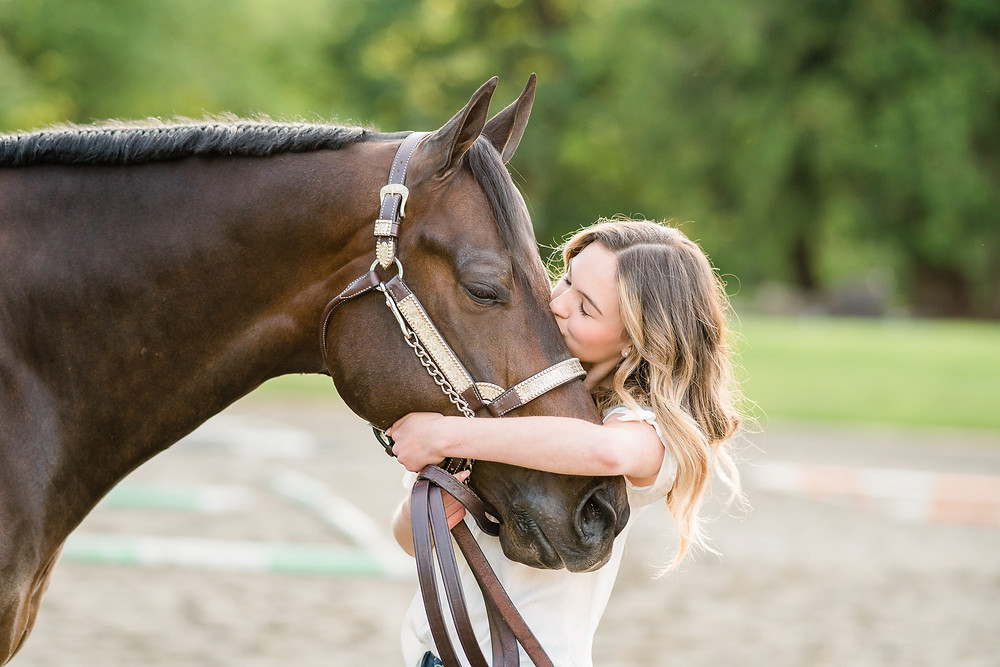 a girl hugging her horse's face while kissing him on the forehead