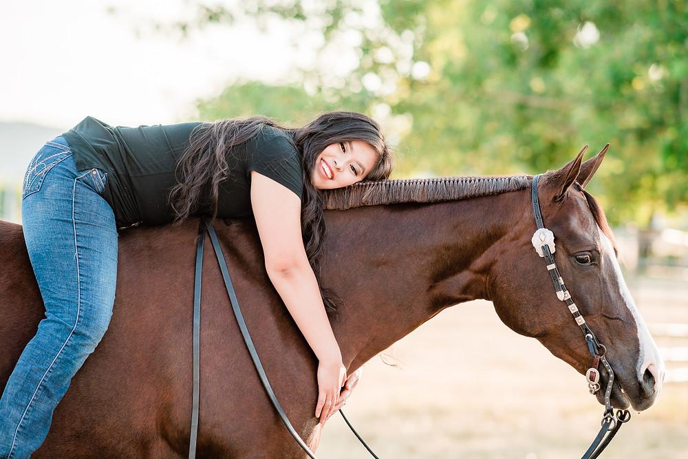 Chloe laying on Marion's neck bareback, hugging her